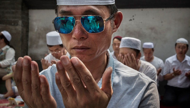 BEIJING, CHINA - JULY 06: Chinese Hui Muslim men pray during Eid al-Fitr prayers marking the end of the holy fasting month of Ramadan at the historic Niujie Mosque on July 6, 2016 in Beijing, China. Islam in China dates back to the 10th century as the legacy of Arab traders who ventured from the Middle East along the ancient Silk Road.  Of an estimated 23 million Muslims in China, roughly half are Hui, who are ethnically Chinese and speak Mandarin.  China's constitution provides for Islam as one of five 'approved' religions in the officially atheist country though the government enforces severe limits.  Worship is permitted only at state-sanctioned mosques and proselytizing in public is illegal.  The Hui, one of 55 ethnic minorities in China (along with the Han majority), have long nurtured a coexistence with the Communist Party and is among the minority groups with political representation at various levels of government. The Hui Muslim population fast from dawn until dusk during Ramadan and it is believed there are more than 20 million members of the community in the country. (Photo by Kevin Frayer/Getty Images)