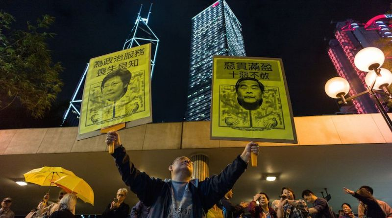 A pro-democracy protester holds up placards featuring (L) Hong Kong's Chief Secretary for Administration Carrie Lam and Chief Executive Leung Chun-Ying during a rally in Hong Kong on December 11, 2016, against a crackdown on pro-democracy lawmakers and an electoral system skewed towards Beijing ahead of elections for a new city leader.   / AFP / Anthony WALLACE        (Photo credit should read ANTHONY WALLACE/AFP/Getty Images)