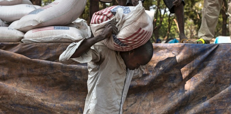 A man unloads a bag of food delivered by USAID, the United States federal government agency primarily reponsible for administering civilian foreign aid, at the Christian refugee camp in Bossangoa on December 19, 2013. The United States today announced $15 million in additional humanitarian aid for the Central African Republic, as a top US envoy was visiting Bangui to press for an end to sectarian bloodshed. AFP PHOTO / FRED DUFOUR        (Photo credit should read FRED DUFOUR/AFP/Getty Images)
