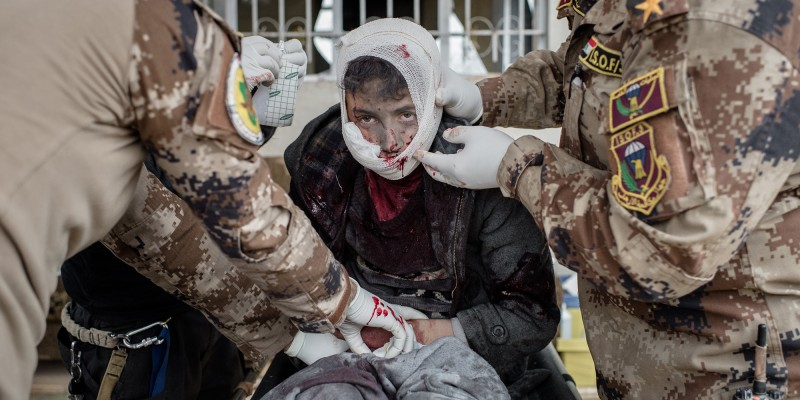 A young boy, wounded by shrapnel in his face and groin, is quickly treated at a clinic in the Samah neighborhood of Mosul, Iraq on Thursday, December 1, 2016. It was unclear if the medics were able to stop the boy's bleeding as he continued to drip blood through the gauze and bandages they wrapped him in before loading him into an ambulance.