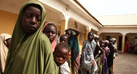 Girls rescued by Nigerian soldiers from Islamist militants Boko Haram at Sambisa Forest line up to collect donated clothes at the Malkohi refugee camp in Yola on May 5, 2015. They were among a group of 275 people rescued by the Nigerian military last week and arrived at the camp on May 2. The Nigerian military said it has rescued some 700 women and children in the past weeks. AFP PHOTO / EMMANUEL AREWA        (Photo credit should read EMMANUEL AREWA/AFP/Getty Images)