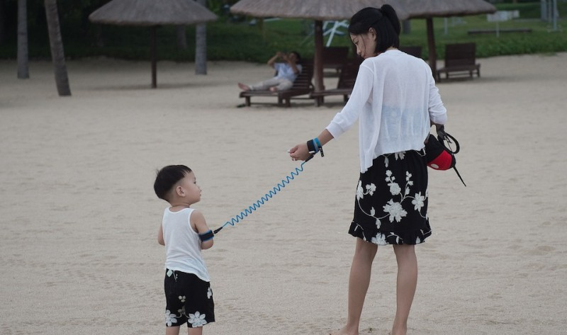 "In this picture taken on October 11, 2016 a mother is using a leash to keep her child nearby at a beach at the Club Med resort in Sanya.  Almost two years after being bought out by Chinese investment fund Fosun, the holiday resort French group Club Med tries to import its recipes on a promising Chinese market, where a growing upper middle-class now discovers the concept - still very new in Chinese society - of holiday resorts. / AFP / NICOLAS ASFOURI / TO GO WITH AFP STORY: ""CHINA-FRANCE-TOURISM-INVESTMENTS-SOCIETY"" Focus by Julien GIRAULT        (Photo credit should read NICOLAS ASFOURI/AFP/Getty Images)"