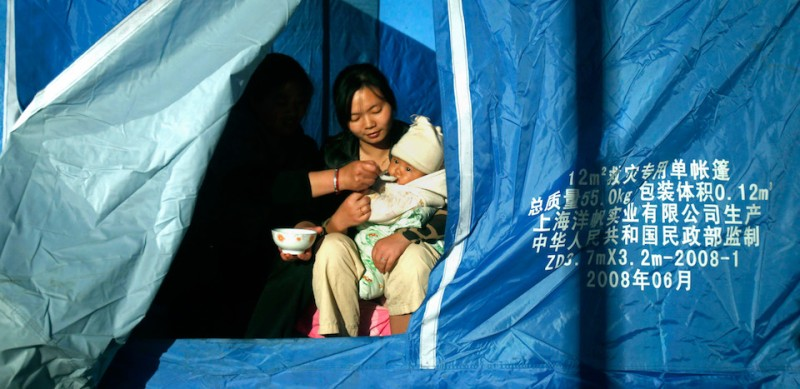 This photo taken on April 23, 2013 shows two woman feeding a baby at a temporary settlement in Yaan, southwest China's Sichuan province. Tens of thousands of homeless survivors of China's devastating quake are living in makeshift tents or on the streets, facing shortages of food and supplies as well as an uncertain future.   CHINA OUT   AFP PHOTO        (Photo credit should read AFP/AFP/Getty Images)