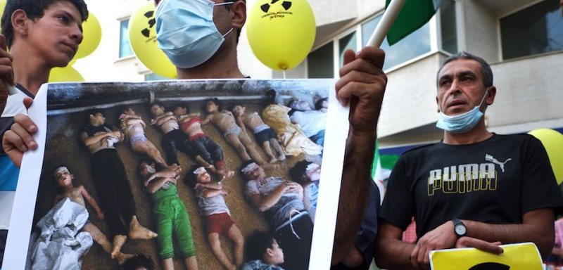 Syrian immigrants living in Bulgaria hold a photo showing the bodies of men, women, and children allegedly killed in a chemical attack east of Damascus as they protest against the regime of Syrian President Bashar Al-Assad and the use of chemical weapons, on August 23, 2013, in front of the Syrian Embassy in Sofia. Horrific images of an alleged chemical weapons attack in Ghouta, east of Damascus, in Syria have shocked the world this week. An opposition alliance says 1,300 people were killed and that chemical gases were unleashed by the Syrian regime, while the government denies any responsibility.   AFP PHOTO / DIMITAR DILKOFF        (Photo credit should read DIMITAR DILKOFF/AFP/Getty Images)