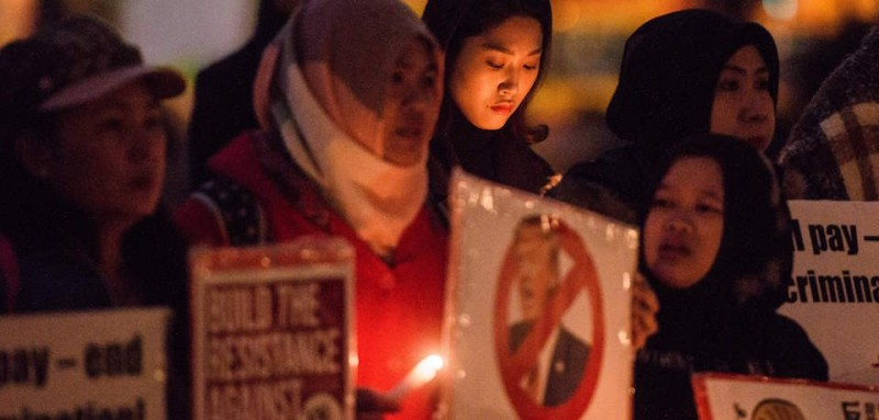 Women hold candles and placards against US President Donald Trump during a vigil to mark International Women's Day (IWD) in Hong Kong on March 8, 2017.  / AFP PHOTO / Anthony WALLACE        (Photo credit should read ANTHONY WALLACE/AFP/Getty Images)