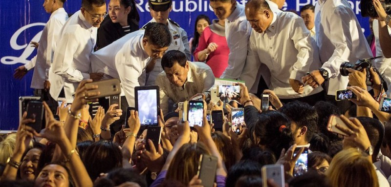 "Philippine President Rodrigo Duterte (C) greets female supporters at the Malacanang Palace during the ""Digong's Day for Women"" event on March 31, 2017.  Philippine President Rodrigo Duterte on March 30 described two major media outlets as ""sons of whores"" and warned them of karmic repercussions for their critical coverage of his deadly drug war. / AFP PHOTO / NOEL CELIS        (Photo credit should read NOEL CELIS/AFP/Getty Images)"