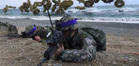 TOPSHOT - South Korean Marines take position on a beach as amphibious assault vehicles fire smoke shells during a joint landing operation by US and South Korean Marines in the southeastern port of Pohang on April 2, 2017. The drill is part of the annual joint exercise Foal Eagle to enhance the combat readiness of the US and South Korea supporting forces in defense of the Korean Peninsula.  / AFP PHOTO / JUNG Yeon-Je        (Photo credit should read JUNG YEON-JE/AFP/Getty Images)