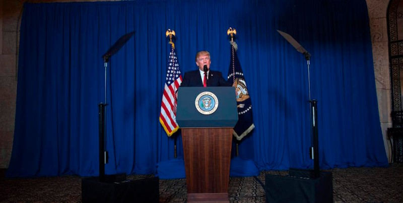 TOPSHOT - US President Donald Trump delivers a statement on Syria from the Mar-a-Lago estate in West Palm Beach, Florida, on April 6, 2017. Trump ordered a massive military strike against a Syria Thursday in retaliation for a chemical weapons attack they blame on President Bashar al-Assad. A US official said 59 precision guided missiles hit Shayrat Airfield in Syria, where Washington believes Tuesday's deadly attack was launched.  / AFP PHOTO / JIM WATSON        (Photo credit should read JIM WATSON/AFP/Getty Images)