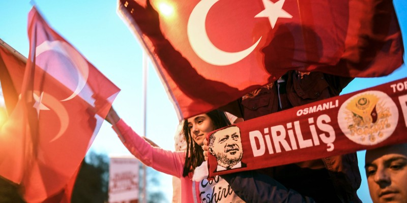 "Supporters of the ""yes"" wave Turkish national flags and scarfs picturing Turkish president Recep Tayyip Erdogan during a rally in front of the president residence, at Sariyer district, in Istanbul, on April 16, 2017, after the initial results of a nationwide referendum that will determine Turkey's future destiny. The ""Yes"" campaign to give Turkish President expanded powers was just ahead in a tightly-contested referendum but the 'No' was closing the gap, according to initial results. / AFP PHOTO / Bulent Kilic        (Photo credit should read BULENT KILIC/AFP/Getty Images)"