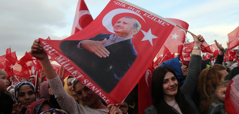 "Supporters of the ""yes"" wave Turkish National flags and flags depicting Turkish president Recep Tayyip Erdogan as they cheer during his speech at the Presidential Palace in Ankara, on April 17, 2017 following the results in a nationwide referendum that will determine Turkey's future destiny. Erdogan on April 17 said Turkey could hold a referendum on its long-stalled EU membership bid after Turks voted to approve expanding the president's powers in a plebiscite. Narrowly won by President Recep Tayyip Erdogan, the referendum asked voters to boost the powers of the Turkish head of state -- a move that rights watchdogs have said could fatally weaken democracy in the linchpin country. / AFP PHOTO / ADEM ALTAN        (Photo credit should read ADEM ALTAN/AFP/Getty Images)"