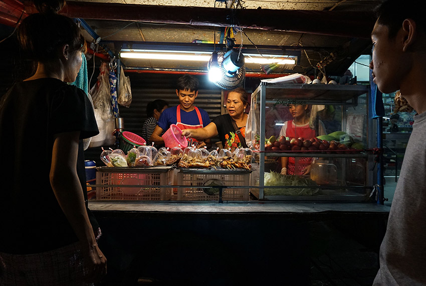 This photo taken on April 17, 2017 shows a family preparing food for customers at a street food stall in the Phrakanong district of Bangkok. Street food stalls will be banned from all of Bangkok's main roads under a clean-up crusade, a city hall official said Tuesday, prompting outcry and anguish in a food-obsessed capital famed for its spicey roadside cuisine.  / AFP PHOTO / LILLIAN SUWANRUMPHA        (Photo credit should read LILLIAN SUWANRUMPHA/AFP/Getty Images)