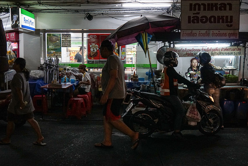 This photo taken on April 17, 2017 shows people walking past a street noodle stall in the Phrakanong district of Bangkok. Street food stalls will be banned from all of Bangkok's main roads under a clean-up crusade, a city hall official said Tuesday, prompting outcry and anguish in a food-obsessed capital famed for its spicey roadside cuisine.  / AFP PHOTO / LILLIAN SUWANRUMPHA        (Photo credit should read LILLIAN SUWANRUMPHA/AFP/Getty Images)