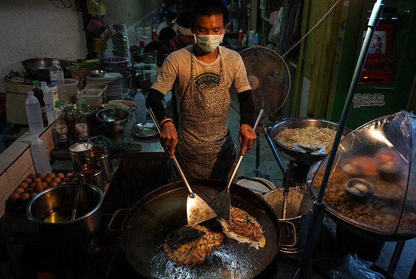 This photo taken on April 17, 2017 shows a man making food at a street stall in the Phrakanong district of Bangkok. Street food stalls will be banned from all of Bangkok's main roads under a clean-up crusade, a city hall official said Tuesday, prompting outcry and anguish in a food-obsessed capital famed for its spicey roadside cuisine.  / AFP PHOTO / LILLIAN SUWANRUMPHA        (Photo credit should read LILLIAN SUWANRUMPHA/AFP/Getty Images)