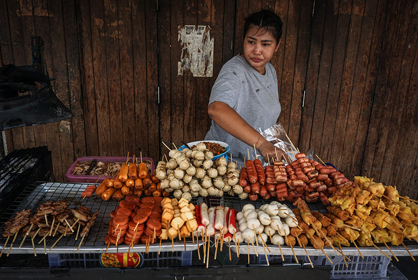 A woman arranges fried snacks on her street food cart the Pratunam district of Bangkok on April 18, 2017.  Street food stalls will be banned from all of Bangkok's main roads under a clean-up crusade, a city hall official said, prompting outcry and anguish in a food-obsessed capital famed for its spicey roadside cuisine. / AFP PHOTO / LILLIAN SUWANRUMPHA        (Photo credit should read LILLIAN SUWANRUMPHA/AFP/Getty Images)