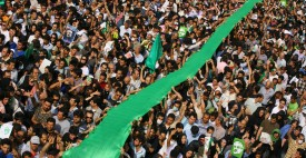 Iranian opposition demonstrators carry a large green flag through the crowd during a demonstration in support of defeated reformist presidential candidate Mir Hossein Mousavi, in Tehran on June 15, 2009, following an election that has divided the nation. Opposition supporters defied a ban to stage a mass rally in Tehran in protest at President Mahmoud Ahmadinejad's landslide election win, as Iran faced a growing international backlash over the validity of the election and the subsequent crackdown on opposition protests.