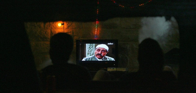 "TO GO WITH AFP STORY BY RIAD ABOU AWAD Palestinians watch an episode of the Syrian TV drama series ""Bab al-Hara"" at a cafe in Arab east Jerusalem, after breaking their fast on August 25, 2009. Arabic television is counting on an explosion of Ramadan serials to restore losses from the global recession, but some concerned Muslims are scrambling to pull the faithful back to prayer during the holy month.   AFP PHOTO /AHMAD GHARABLI (Photo credit should read AHMAD GHARABLI/AFP/Getty Images)"