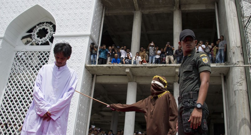An Indonesian Sharia police whips a man during a public caning ceremony outside a mosque in Banda Aceh, capital of Aceh province on September 18, 2015. Three women and 14 men arrested for sexual offenses and gambling were caned in front of the mosque in full view of the public following the Friday prayer. Aceh is the only province of Indonesia that is enforcing the Islamic Sharia law and violators are punished by public caning.  AFP PHOTO / CHAIDEER MAHYUDDIN        (Photo credit should read CHAIDEER MAHYUDDIN/AFP/Getty Images)