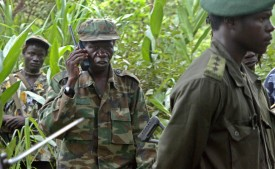 NABANGA, SUDAN:  Uganda's rebel leader, Joseph Kony's second in command, Vincent Otti (C) talks on a communication device as he walks 12 July 2006 through the jungle into a clearing in Nabanga, south Sudan, near the Ugandan and D.R. Congo borders. The venue is to be the stage for a meeting between the mediating south Sudan Government and the infamous Ugandan rebel movement, Lord's Resistance Army (LRA) officials in a bid to a truce negotiation. Just a day after peace talks began 19 July 2006 under Sudanese mediation, the Ugandan government flatly rejected demands for a truce from the rebel Lord's Resistance Army (LRA) and said there could be no ceasefire until a full peace settlement is reached. AFP PHOTO/MATT BROWN  (Photo credit should read MATT BROWN/AFP/Getty Images)