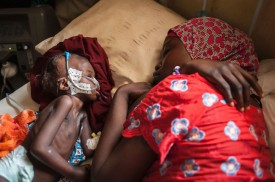 TOPSHOT - A woman and a young girl young child suffering from severe malnutrition sleep on a bed in the ICU ward at the In-Patient Therapeutic Feeding Centre in the Gwangwe district of Maiduguri, the capital of Borno State, northeastern Nigeria, on September 17, 2016.  Aid agencies have long warned about the risk of food shortages in northeast Nigeria because of the conflict, which has killed at least 20,000 since 2009 and left more than 2.6 million homeless. In July, the United Nations said nearly 250,000 children under five could suffer from severe acute malnutrition this year in Borno state alone and one in five -- some 50,000 -- could die. But despite the huge numbers involved, the situation has received little attention compared with other humanitarian crises around the world -- even within Nigeria. / AFP / STEFAN HEUNIS        (Photo credit should read STEFAN HEUNIS/AFP/Getty Images)