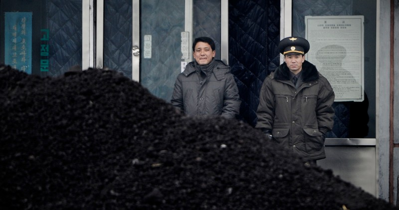 This picture taken on December 14, 2012 from China's northeastern city of Dandong, looking across the border, shows a North Korean military officer (R) and a North Korea man (L) standing behind a pile of coal along the banks of the Yalu River in the northeast of the North Korean border town of Siniuju.  China is North Korea's biggest trading partner by far, and most of the business passes through Dandong in northeastern China, where lorries piled high with tyres and sacks are processed at the customs post.  AFP PHOTO / WANG ZHAO        (Photo credit should read WANG ZHAO/AFP/Getty Images)