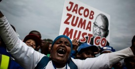 "TOPSHOT - A Democratic Alliance (DA) party's supporters holds a placard reading ""Jacob Zuma must go"" during a march against South African president Jacob Zuma on April 7, 2017 in Johannesburg. Thousands of protesters marched through South African cities on April 7, 2017 demanding President Jacob Zuma's resignation, as a second ratings agency downgraded the country's debt to junk status. Zuma's sacking of respected finance minister Pravin Gordhan last week has fanned public anger, divisions within the ruling ANC party and a sharp decline in investor confidence in the country.  / AFP PHOTO / JOHN WESSELS        (Photo credit should read JOHN WESSELS/AFP/Getty Images)"