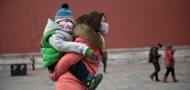 A woman and baby wearing face masks walk in the Forbidden City during heavy pollution in Beijing on February 28, 2013. Beijing residents were urged to stay indoors as pollution levels soared before a sandstorm brought further misery to China's capital. AFP PHOTO / Ed Jones        (Photo credit should read Ed Jones/AFP/Getty Images)