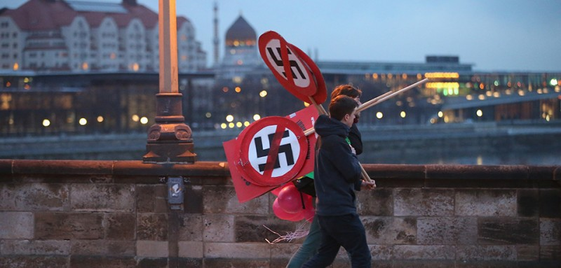 DRESDEN, GERMANY - FEBRUARY 13:  Anti-neo-Nazi activists carry signs showing smarked through swastikas before the creation of a human chain in the city center as a statement against neo-Nazis on the 69th anniversary of the World War II firebombing of the city by the Allies on February 13, 2014 in Dresden, Germany. Neo-Nazis from across Germany have used the anniversary to parade in Dresden in recent years, though a strong, local grass movement against them has prevented their marches and this year led to the cancellation of a neo-Nazi gathering.  (Photo by Sean Gallup/Getty Images)