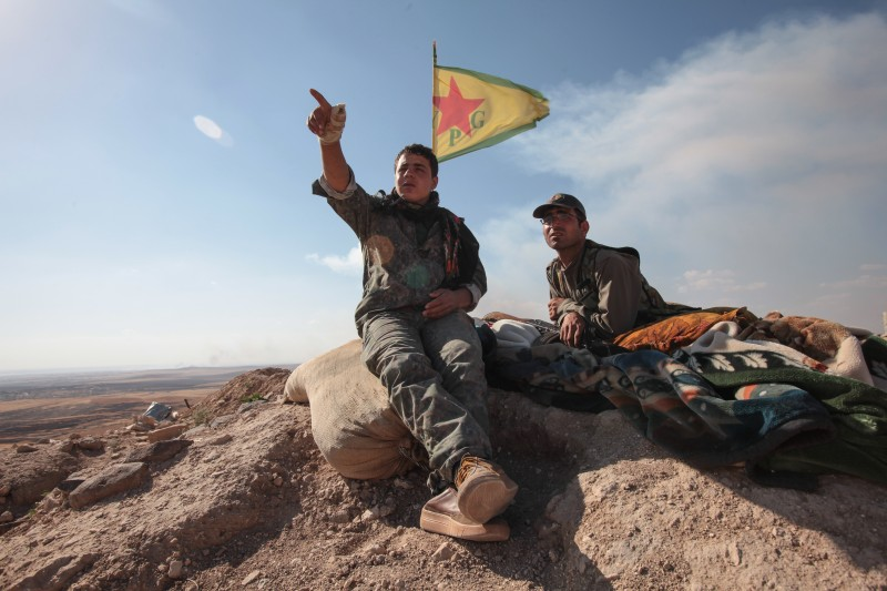 KOBANE, SYRIA - JUNE 20: (TURKEY OUT) A Kurdish People's Protection Units, or YPG fighters sit near a check point in the outskirts of the destroyed Syrian town of Kobane, also known as Ain al-Arab, Syria. June 20, 2015. Kurdish fighters with the YPG took full control of Kobane and strategic city of Tal Abyad, dealing a major blow to the Islamic State group's ability to wage war in Syria. Mopping up operations have started to make the town safe for the return of residents from Turkey, after more than a year of Islamic State militants holding control of the town. (Photo by Ahmet Sik/Getty Images)
