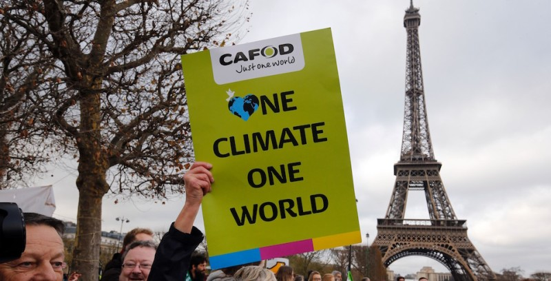 "A demonstrator holds a banner reading ""One climate one world"" during a rally held by several Non Governmental Organisations (NGO)  to form a human chain on the Champs de Mars near the Eiffel Tower in Paris on December 12, 2015 on the sidelines of the COP21, the UN conference on global warming. French hosts submit the final version of a global climate-saving pact to negotiators at UN Conference on december 12. The goal is for ministers to approve the agreement by the end of the day but that could be extended one more day. / AFP / FRANCOIS GUILLOT        (Photo credit should read FRANCOIS GUILLOT/AFP/Getty Images)"