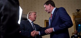 """WASHINGTON, DC - JANUARY 22: U.S. President Donald Trump (C) shakes hands with James Comey, director of the Federal Bureau of Investigation (FBI), during an Inaugural Law Enforcement Officers and First Responders Reception in the Blue Room of the White House on January 22, 2017 in Washington, DC. Trump today mocked protesters who gathered for large demonstrations across the U.S. and the world on Saturday to signal discontent with his leadership, but later offered a more conciliatory tone, saying he recognized such marches as a """"hallmark of our democracy."""" (Photo by Andrew Harrer-Pool/Getty Images)"""