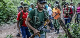"FARC guerrillas march in column during a review at their camp in the Transitional Standardization Zone in Pondores, La Guajira department, Colombia on April 3, 2017. The Colombian government reported that the FARC guerrillas provided a total list with the names of the 6,084 members of the rebel group who have gathered in 26 ""standardization zones"" across the country, where they are building accomodations that will house them until the end of the disarmament process, outlined in the peace agreement reached in November 2016. / AFP PHOTO / Joaquin Sarmiento        (Photo credit should read JOAQUIN SARMIENTO/AFP/Getty Images)"