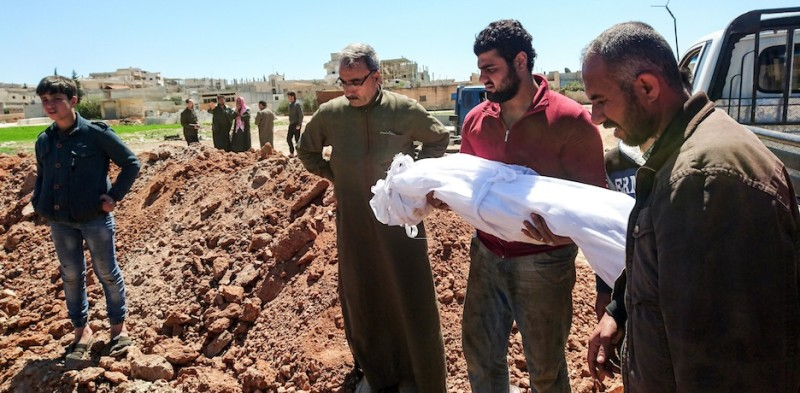 Syrians bury the bodies of victims of a a suspected toxic gas attack in Khan Sheikhun, a nearby rebel-held town in Syrias northwestern Idlib province, on April 5, 2017. International outrage is mounting over a suspected chemical attack that killed scores of civilians in Khan Sheikhun on April 4, 2017.  Warplanes had carried out a suspected toxic gas attack that killed dozens people including several children, a monitoring group said.  The Syrian Observatory for Human Rights said those killed in the town of Khan Sheikhun, in Idlib province, had died from the effects of the gas, adding that dozens more suffered respiratory problems and other symptoms. / AFP PHOTO / FADI AL-HALABI        (Photo credit should read FADI AL-HALABI/AFP/Getty Images)