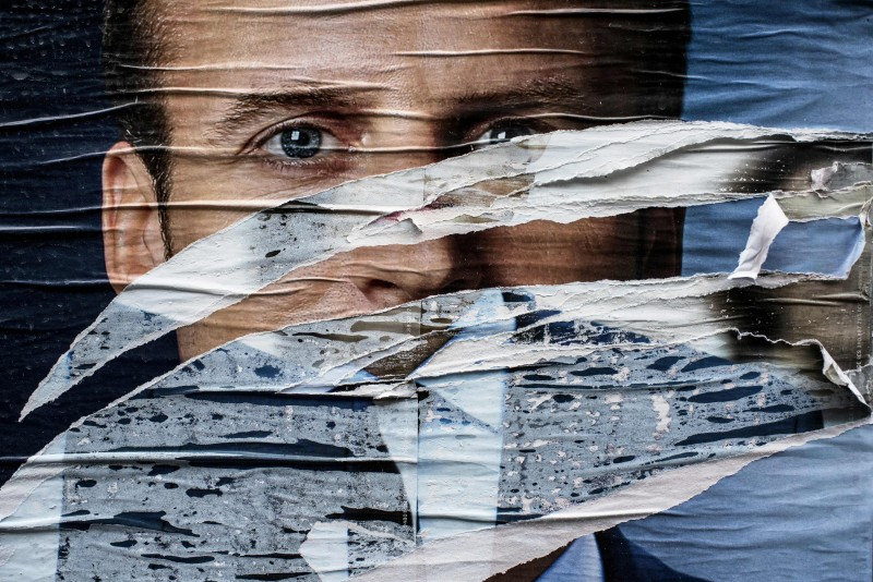 A picture shows a vandalised campaign poster of French presidential candidate Emmanuel Macron (L) of the En Marche ! movement in Lyon on May 1, 2017 ahead of the second and final round of the French presidential election on May 7. / AFP PHOTO / JEFF PACHOUD        (Photo credit should read JEFF PACHOUD/AFP/Getty Images)