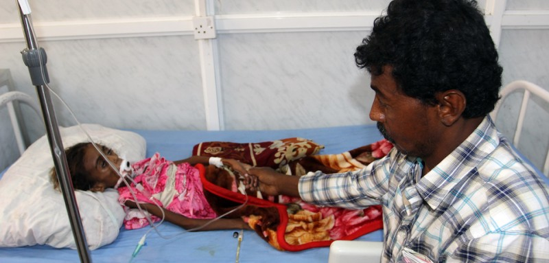 A Yemeni tends to his malnourished child as she receives treatment at a hospital in the Yemeni port city of Hodeidah, on May 2, 2017.  / AFP PHOTO / STR        (Photo credit should read STR/AFP/Getty Images)