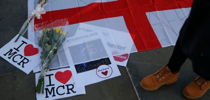 Posters, a flag and a bunch of flowers in solidarity with the dead and injured from the terror attack in Manchester are arranged on the pavement in Trafalgar Square in central London on May 23, 2017.  Twenty two people have been killed and dozens injured in Britain's deadliest terror attack in over a decade after a suspected suicide bomber targeted fans leaving a concert of US singer Ariana Grande in Manchester. British police on Tuesday named the suspected attacker behind the Manchester concert bombing as Salman Abedi, but declined to give any further details. / AFP PHOTO / Daniel LEAL-OLIVAS        (Photo credit should read DANIEL LEAL-OLIVAS/AFP/Getty Images)