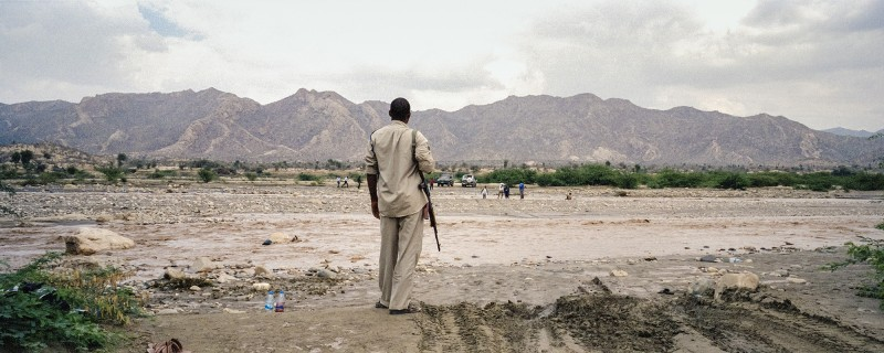 Outside Geerisa, Somalia: An armed policeman stands beside a riverbank swelled from a flash flood the night before that left several people dead. As Somalia gets hotter and drier, it is also more susceptible to deadly flash floods when eventual rain hits the parched earth.  To be Somali used to mean to roam the land with your camels and others herds, surviving on their milk and meat and making home wherever the rains fell. Three out of four Somalis depend on the land to survive, either by herding or farming. Yet the rains are becoming less frequent and drought the norm. Land is degraded out of desperation, and people's historic resilience is broken down. As access to water and pasture shrink, so do people's options. The result is a growing wave of violence that swells with each short rain, dry well and failed crop. Men with guns are as common here as dusty roads, and as the fragile ties linking communities together break down the choice becomes clear: fight or die. (Photo by Nichole Sobecki)