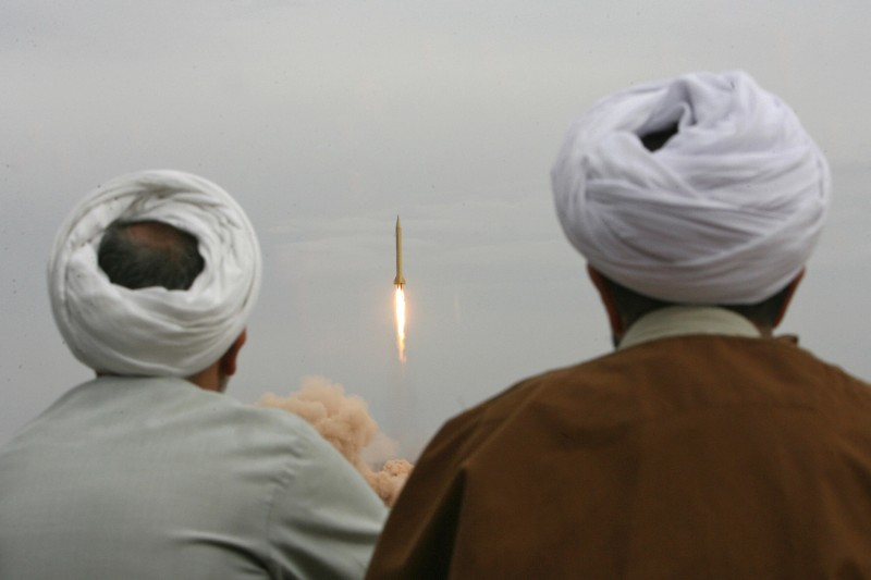 QOM, IRAN:  Iranian clergymen watch a Shahab-3 long-range ballistic missile fird by Iran's Revolutionary Guards in the desert outside the holy city of Qom, 02 November 2006. The Islamic republic fired its longer-range missile on exercise for the first time today as it began 10 days of war games amid a mounting standoff with the West over its nuclear programme. The hardline Revolutionary Guards fired the missiles, which have a range of up to 2,000 kilometres (1,200 miles) -- sufficient to threaten US bases in the Gulf -- during the first phase of the manoeuvres in the central desert, state television reported.  AFP PHOTO/FARS NEWS  (Photo credit should read -/AFP/Getty Images)