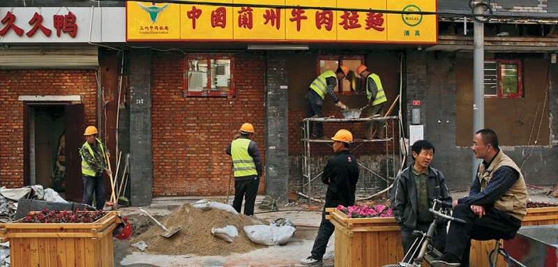 Workers erect a brick wall at the former shop front of a restaurant in a hutong neighborhood near the Forbidden City in Beijing, China April 20, 2017.  REUTERS/Thomas Peter - RTS1340S