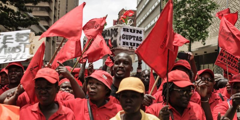 """Protesters carry a cardboard mock up coffin reading 'Run Guptas run' and with the names of the people implicated in the Public Protector """"State Capture"""" report as members and supporters of the South African opposition party, the Economic Freedom Fighters (EFF), demonstrate against South African president Jacob Zuma and in support of the release of the South African Public Protector """"State Capture"""" report in Pretoria on November 2, 2016.  South Africa's anti-corruption watchdog on November 2 called for prosecutors to investigate alleged criminal activity as it released a report into President Jacob Zuma that fuelled further calls for him to resign. Zuma, whose presidency has been engulfed by multiple scandals, had fought to block the release of the Public Protector's report, but his lawyers made a surprise U-turn and dropped their legal appeal. The report was released hours later, further undermining Zuma after a series of court rulings that have tarnished his time in office and the ruling ANC party that led the fight to end apartheid rule. / AFP / GIANLUIGI GUERCIA        (Photo credit should read GIANLUIGI GUERCIA/AFP/Getty Images)"""