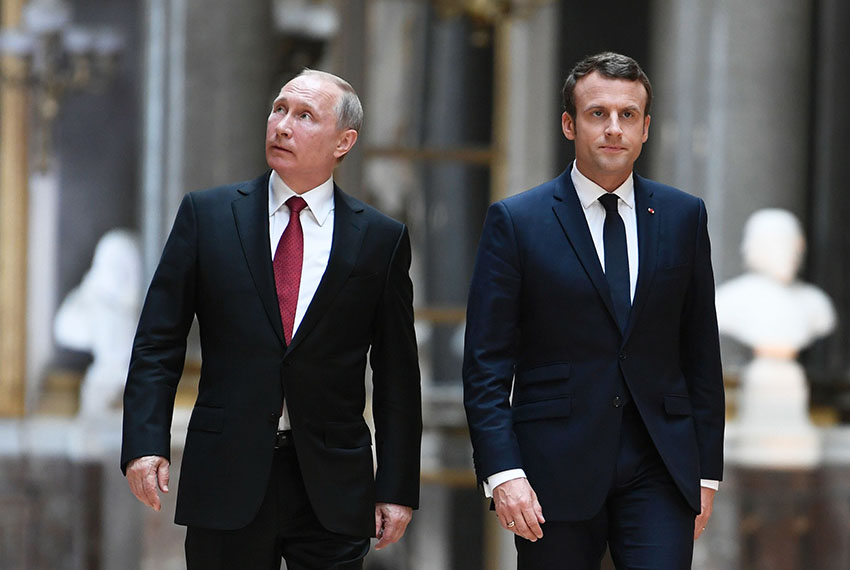 Russian President Vladimir Putin (L) looks around in the Galerie des Batailles (Gallery of Battles) as he arrives with French President Emmanuel Macron (R) for a joint press conference following their meeting at the Versailles Palace, near Paris, on May 29, 2017. French President Emmanuel Macron hosts Russian counterpart Vladimir Putin in their first meeting since he came to office with differences on Ukraine and Syria clearly visible. / AFP PHOTO / POOL / STEPHANE DE SAKUTIN        (Photo credit should read STEPHANE DE SAKUTIN/AFP/Getty Images)