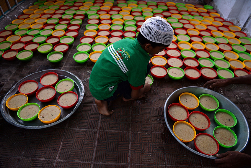 TOPSHOT - An Indian Muslim boy arranges rows of food for Iftar, the time for breaking the fast during the first day of the month of Ramadan at Wallajah Mosque in Chennai on May 28, 2017. Like millions of Muslim around the world, Indian Muslims celebrated the month of Ramadan by abstaining from eating, drinking, and smoking as well as sexual activities from dawn to dusk. / AFP PHOTO / ARUN SANKAR        (Photo credit should read ARUN SANKAR/AFP/Getty Images)