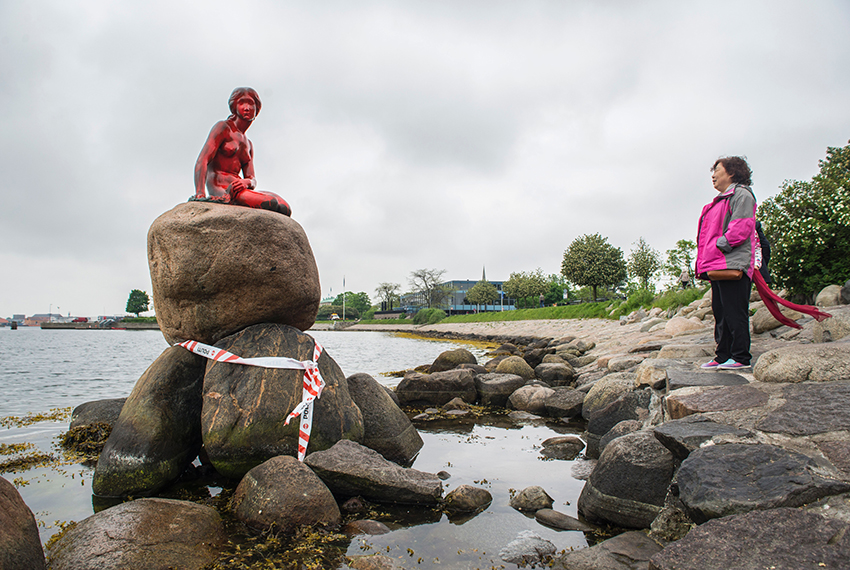 A woman looks at Copenhagen's world famous statue of The Little Mermaid that has been exposed to vandalism and was painted red on May 30, 2017. / AFP PHOTO / Scanpix Denmark / Ida Marie Odgaard / Denmark OUT        (Photo credit should read IDA MARIE ODGAARD/AFP/Getty Images)