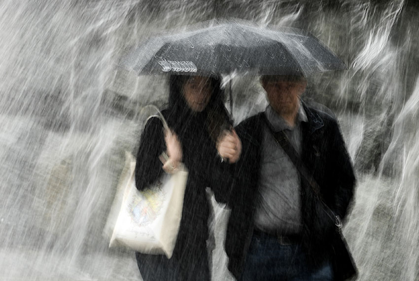 TOPSHOT - A couple protects themselves with an umbrella while walking under heavy rain in Moscow's Alexander Garden on May 29, 2017. / AFP PHOTO / Kirill KUDRYAVTSEV        (Photo credit should read KIRILL KUDRYAVTSEV/AFP/Getty Images)