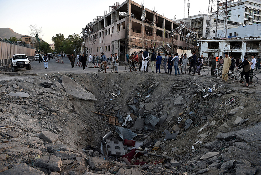 TOPSHOT - Afghan security forces and residents stand near the crater left by a truck bomb attack in Kabul on May 31, 2017. At least 80 people were killed and hundreds wounded May 31 when a massive truck bomb ripped through Kabul's diplomatic quarter, bringing carnage to the streets of the Afghan capital and shattering windows hundreds of metres away. / AFP PHOTO / WAKIL KOHSAR        (Photo credit should read WAKIL KOHSAR/AFP/Getty Images)