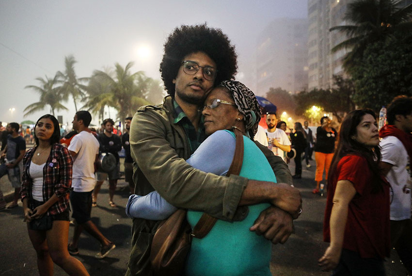 RIO DE JANEIRO, BRAZIL - MAY 28:  Orlando Caldeira embraces his mother Georgina at a demonstration and concert calling for direct presidential elections on May 28, 2017 in Rio de Janeiro, Brazil. President Michel Temer is enmired in allegations of endorsing bribery in a scandal which threatens to bring down his brief presidency.  (Photo by Mario Tama/Getty Images)