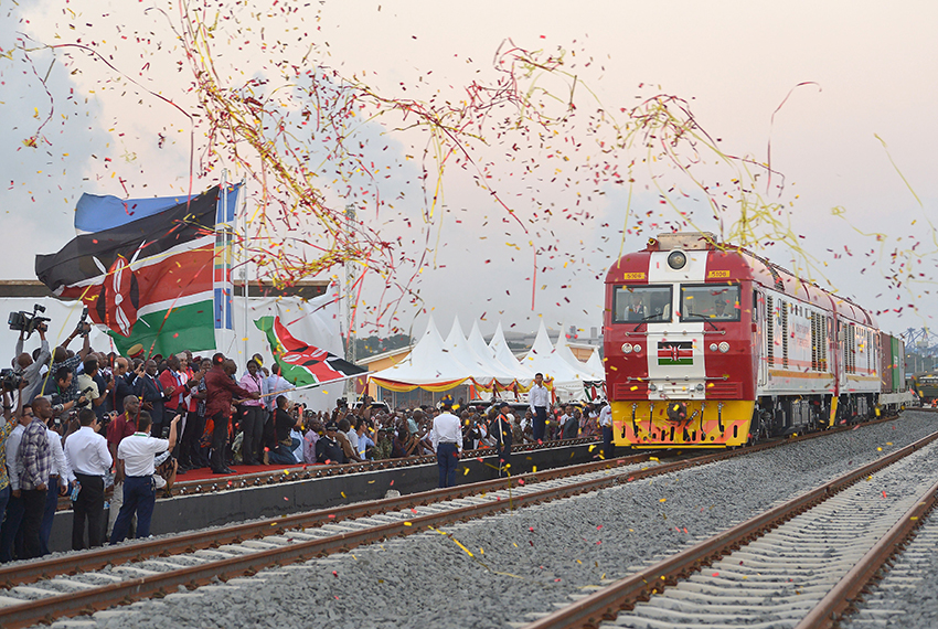 TOPSHOT - Kenyan President Uhuru Kenyatta flags off a cargo train, as it leaves the container terminal for its inaugural journey to Nairobi, at the port of the coastal town of Mombasa on May 30, 2017. More than a century after a colonial railway gave birth to modern Kenya, the country is betting on a new Chinese-built route to cement its position as the gateway to East Africa. The $3.2 billion (2.8 billion euro) railway linking Nairobi with the port city of Mombasa will May 31 take its first passengers on the 472 kilometre (293 mile) journey, allowing them to skip a hair-raising drive on one of Kenya's most dangerous highways.  / AFP PHOTO / TONY KARUMBA        (Photo credit should read TONY KARUMBA/AFP/Getty Images)