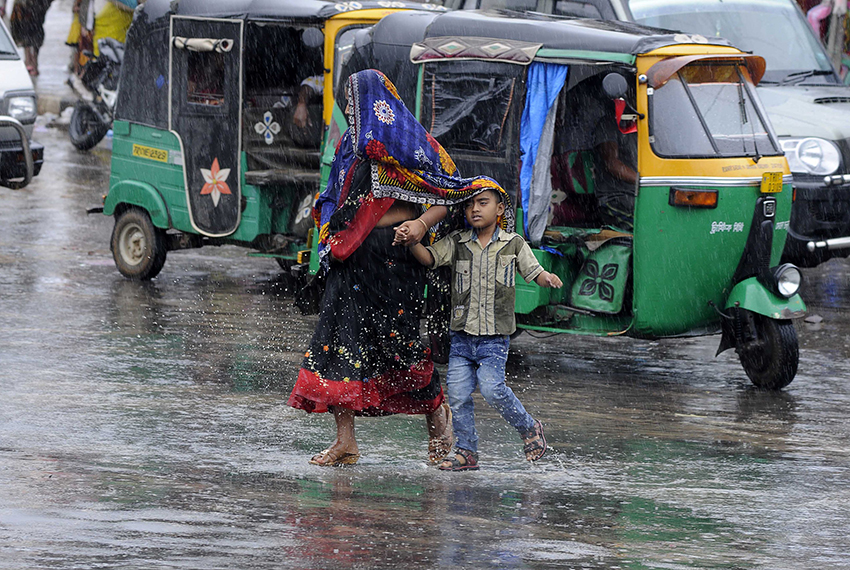 TOPSHOT - An Indian woman and child cross a road in heavy rain brought by Cyclone Mora, in Agartala, the capital of northeastern state of Tripura, on May 30, 2017. Rain brought by Cyclone Mora hit northeastern Indian states with authorities issuing a high wind warning. / AFP PHOTO / Arindam DEY        (Photo credit should read ARINDAM DEY/AFP/Getty Images)