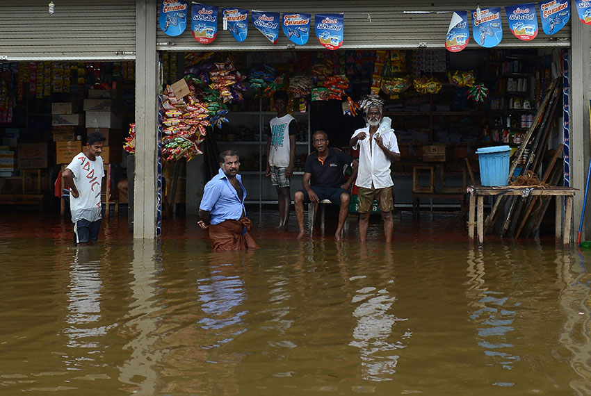 TOPSHOT - Sri Lankan residents look on from a shop surrounded by floodwaters in Nagoda in Kalutara district on May 29, 2017. Sri Lanka's monsoon toll climbed to 164 with the discovery of more bodies of people buried in landslides triggered by intense rains, the Disaster Management Centre (DMC) said May 29.  / AFP PHOTO / LAKRUWAN WANNIARACHCHI        (Photo credit should read LAKRUWAN WANNIARACHCHI/AFP/Getty Images)