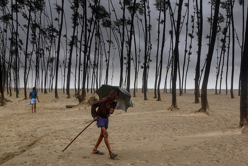 TOPSHOT - A Bangladeshi villager evacuates to a cyclone shelter on the coast in Cox's Bazar district on May 30, 2017. Cyclone Mora hit Bangladesh on May 30, packing winds of up to 135 kilometres (84 miles) per hour, damaging thousands of homes as more than 300,000 people fled coastal villages.  / AFP PHOTO / -        (Photo credit should read -/AFP/Getty Images)