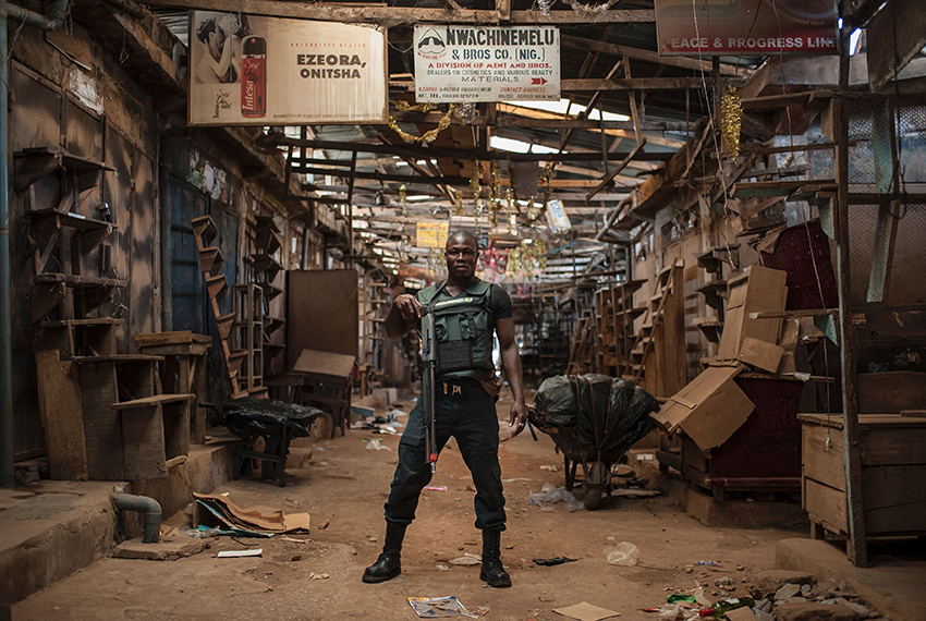 TOPSHOT - A security guard poses for a photo in an empty ally way in Ogbaru Market on May 30, 2017, during a shutdown in commemoration of the 50th anniversary of the Nigerian Civil War.  Nigeria on May 30 marks 50 years since the declaration of an independent Republic of Biafra plunged the country into a civil war, amid renewed tensions and fresh calls for a separate state. The main pro-independence groups -- the Indigenous People of Biafra (IPOB), and the Movement for the Actualisation of the Sovereign State of Biafra (MASSOB) -- have called for a day of reflection. / AFP PHOTO / STEFAN HEUNIS        (Photo credit should read STEFAN HEUNIS/AFP/Getty Images)